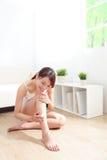 Donna graziosa che applica crema sulle sue gambe attraenti Fotografia Stock Libera da Diritti