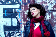 Donna graziosa che aspetta alla parete dei graffiti Fotografie Stock Libere da Diritti