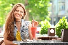 Donna graziosa che beve frullato saporito immagini stock libere da diritti