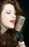 Donna graziosa che canta nel microfono Fotografia Stock Libera da Diritti