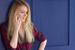 Donna graziosa che chiama qualcuno tramite il telefono cellulare mentre sorridendo Immagine Stock Libera da Diritti