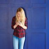 Donna graziosa che chiama qualcuno tramite il telefono cellulare mentre sorridendo Immagini Stock