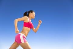Donna graziosa che corre da solo al giorno soleggiato Fotografia Stock