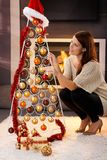 Donna graziosa che decora l'albero di Natale moderno Immagini Stock Libere da Diritti