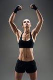 Donna graziosa che dimostra i suoi forti muscoli Immagine Stock