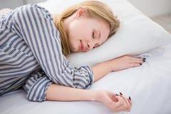 Donna graziosa che dorme nel suo letto sul cuscino Fotografie Stock
