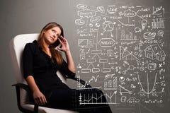 Donna graziosa che esamina i grafici ed i simboli del mercato azionario Fotografie Stock Libere da Diritti