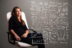 Donna graziosa che esamina i grafici ed i simboli del mercato azionario Immagini Stock Libere da Diritti