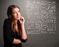 Donna graziosa che esamina i grafici ed i simboli del mercato azionario Fotografia Stock