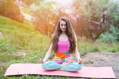 Donna graziosa che fa gli esercizi di yoga sul paesaggio della natura Immagine Stock Libera da Diritti