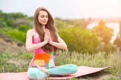 Donna graziosa che fa gli esercizi di yoga sul paesaggio della natura fotografia stock