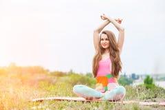 Donna graziosa che fa gli esercizi di yoga sul paesaggio della natura Fotografie Stock