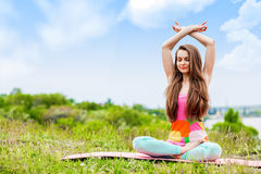 Donna graziosa che fa gli esercizi di yoga sul paesaggio della natura Fotografia Stock Libera da Diritti