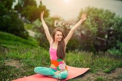 Donna graziosa che fa gli esercizi di yoga sul paesaggio della natura Immagini Stock