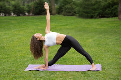 Donna graziosa che fa le esercitazioni di yoga Immagine Stock