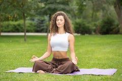 Donna graziosa che fa le esercitazioni di yoga Immagini Stock