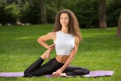 Donna graziosa che fa le esercitazioni di yoga Fotografie Stock