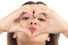 Donna graziosa che fa una forma del cuore con le sue mani Fotografie Stock
