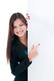 Donna graziosa che indica alla scheda in bianco Fotografia Stock