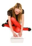 Donna graziosa che lavora con il computer portatile sul pavimento Fotografia Stock