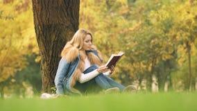 Donna graziosa che legge libro interessante, sedendosi sotto l'albero, spendente tempo libero stock footage