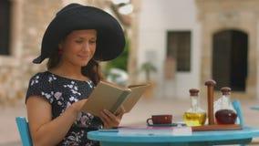 Donna graziosa che legge vecchio tascabile in caffè, godendo del resto, rilassantesi sulla vacanza video d archivio