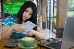 Donna graziosa che manda un sms nel self-service Immagine Stock