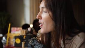 Donna graziosa che mangia l'hamburger degli alimenti a rapida preparazione al caffè stock footage
