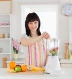Donna graziosa che mette le verdure in un miscelatore Immagine Stock