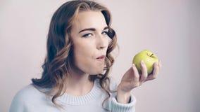 Donna graziosa che morde una mela verde e che esamina macchina fotografica archivi video