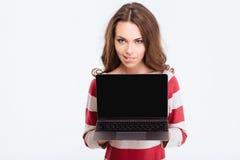 Donna graziosa che mostra lo schermo in bianco del compter del computer portatile Fotografia Stock
