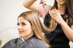 Donna graziosa che ottiene un taglio di capelli fotografie stock