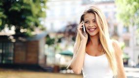Donna graziosa che parla sul suo telefono cellulare mentre cammina bella via europea Giovane ragazza felice nella camminata della archivi video