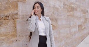 Donna graziosa che parla sul telefono e che si appoggia parete archivi video