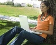 Donna graziosa che per mezzo del computer portatile Immagini Stock
