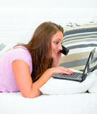 Donna graziosa che per mezzo del computer portatile e comunicando sul telefono Immagine Stock