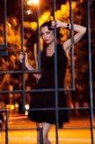 Donna graziosa che posa nella gabbia all'aperto alla notte Fotografia Stock Libera da Diritti