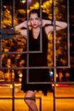 Donna graziosa che posa nella gabbia all'aperto alla notte Immagini Stock