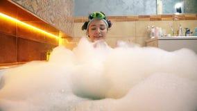 Donna graziosa che prende bagno spumoso e che gioca con la schiuma del sapone fotografia stock libera da diritti