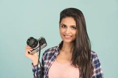 Donna graziosa che prende una foto facendo uso della macchina fotografica classica dello slr fotografia stock libera da diritti