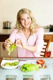Donna graziosa che produce insalata Immagini Stock