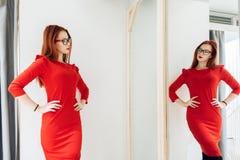 Donna graziosa che prova sui vestiti in un negozio adatto la signora in rosso si veste è riflessa nello specchio immagine stock libera da diritti
