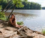 Donna graziosa che si distende da Lake fotografia stock libera da diritti