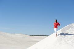 Donna graziosa che si leva in piedi sicura sulla duna del deserto Immagine Stock