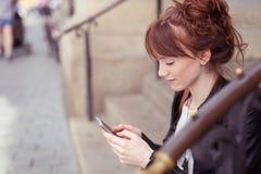 Donna graziosa che si siede sui punti per leggere gli sms Fotografie Stock