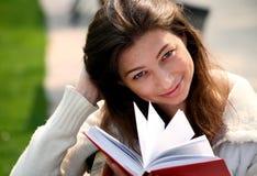 Donna graziosa che si siede sul banco in libro di lettura della sosta Fotografie Stock Libere da Diritti