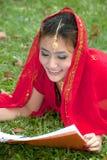 Donna graziosa che si trova leggendo un libro. immagini stock