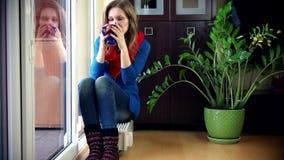 Donna graziosa che sorride alla macchina fotografica che si siede sul radiatore e sul tè caldo bevente stock footage