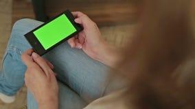 Donna graziosa che tiene Smart Phone disponibile con la visualizzazione verde stock footage