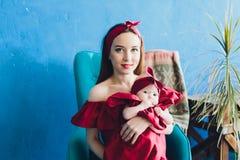 Donna graziosa che tiene un neonato lei armi fotografie stock libere da diritti